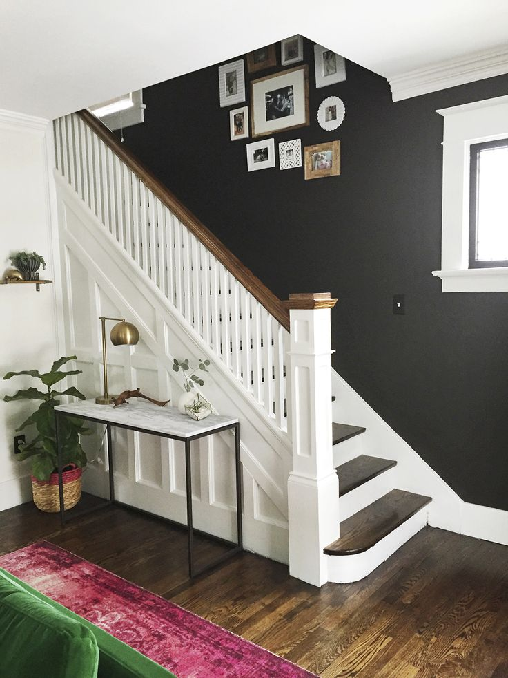 Beautiful entryway and staircase makeover with dark wall and white stairs and woodwork
