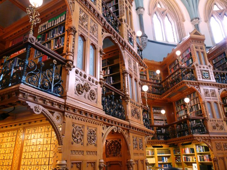 Reading Room in Library of Parliament, Ottawa, Ontario, Canada - The room is paneled in white pine with fantastical carvings of flowers, gargoyle masks, and mythical beasties, dozens of cubby holes for books.