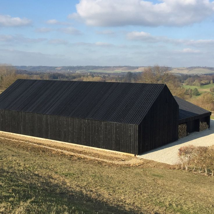 Macdonald Wright Architects has added a barn clad in black-stained boards toCaring Wood – a Kent country villa that is vying to be named the UK's House of the Year