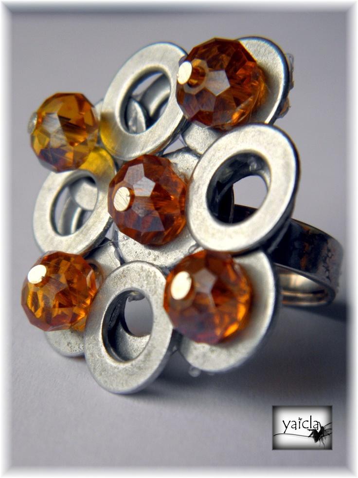 Este mes se trata de crear joyas con elementos de ferretera.En mi primera propuesta del mes me decante por las puntas,esta vez he preferido las arandelas.  Como veis se trata de una anillo donde se van superponiendo dos capas de arandelas,luego en el centro de algunas de ellas facetadas en color naranja,atravesadas por bastones en color plata.