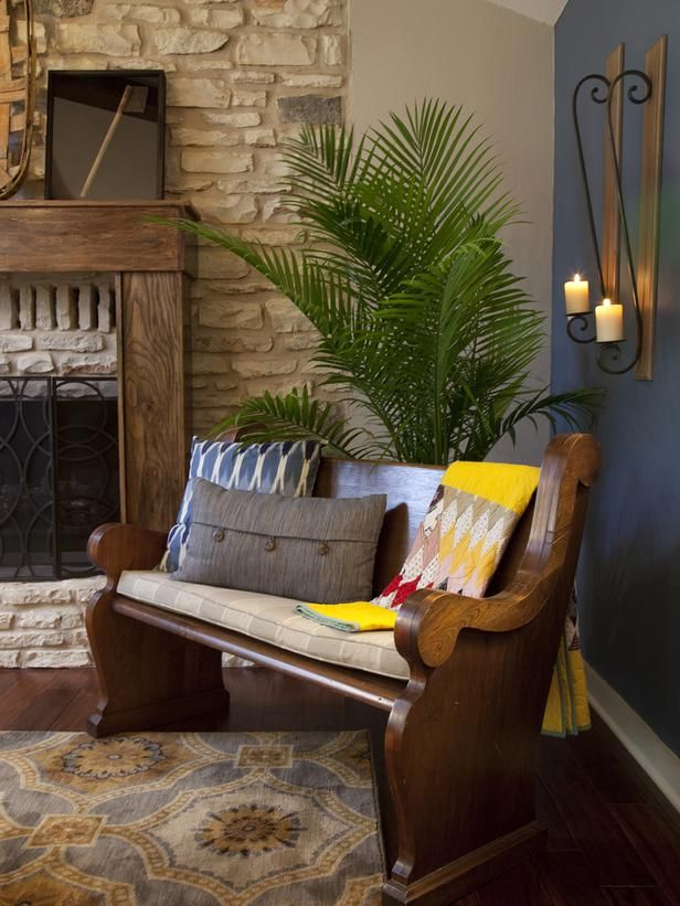A church pew given to the homeowner by his grandfather is repurposed as a bench, adding sentimental value to this living room designed by HG...