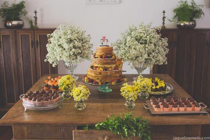 Organização da mesa: bolo no meio com um arranjo de flores em cada lado e duas bandejas de doces alocadas mais à frente, uma de cada lado.