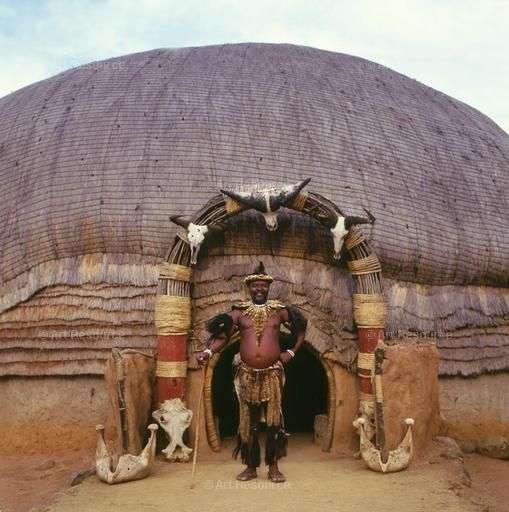 Africa    Zulu man in tribal dress standing outside his beehive hut, Natal, South Africa   ©Stephanie Colasanti