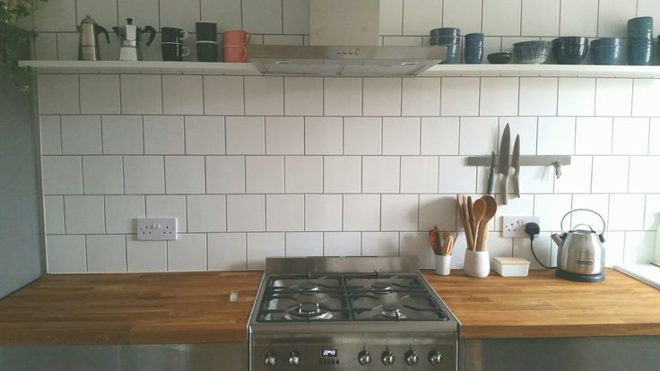 Square white tiles, solid wood worktops, single shelf.