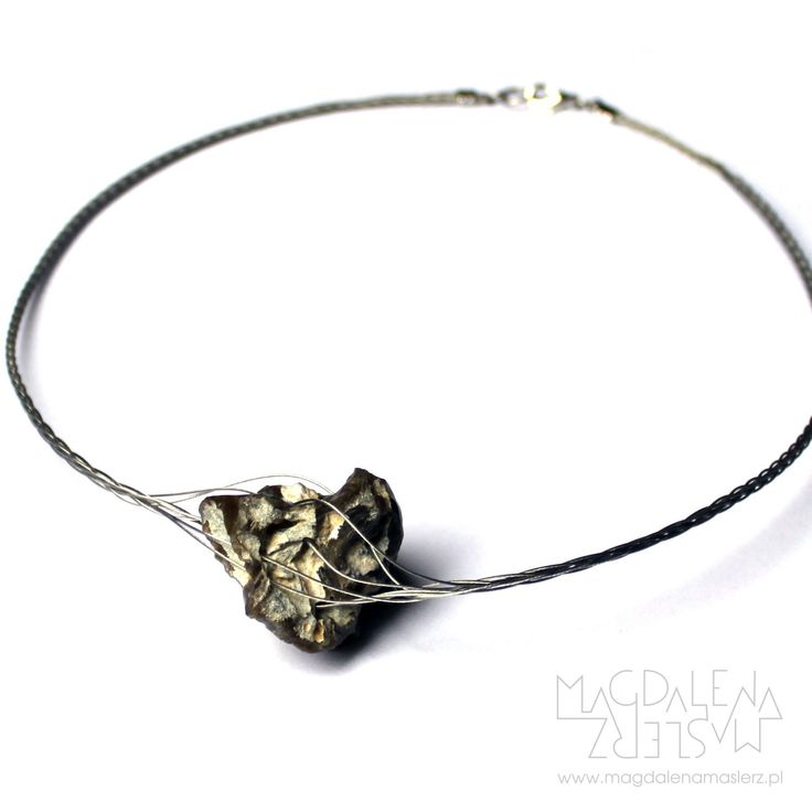 magdalena maślerz - a necklace with a stone with many natural holes, braided with jewelers strings. 2011