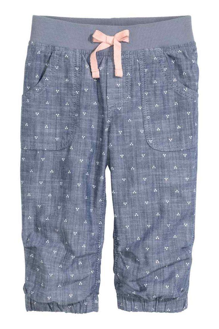 Katoenen pull-on broek: Een pull-on broek van geweven katoen met elastiek en een decoratief trekkoord in de taille. De broek heeft een siergulp, steek- en achterzakken en elastiek onder aan de pijpen.