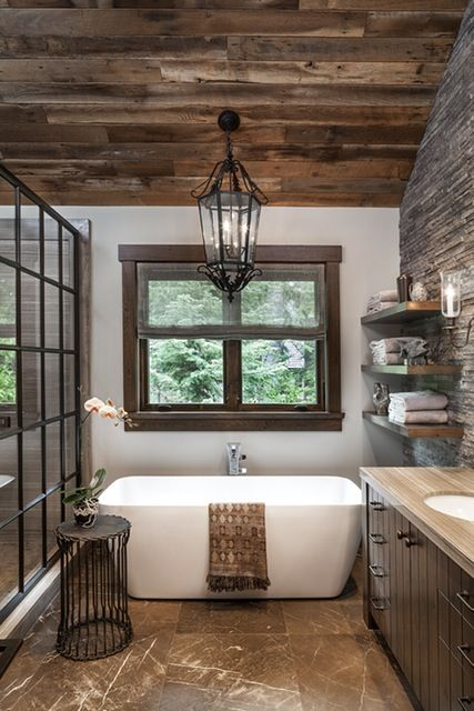 A vintage light from Paris hangs above the tub in the master bathroom, which is accented by a side table from Formations. The iron and glass shower enclosure was custom designed. The shade fabric is from Schumacher.