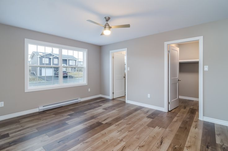 The master bedroom of this new custom built home in Bristolwood has beautiful laminate flooring, a convenient ensuite bathroom and spacious walk-in closet. Another beautiful home from Donovan Homes!