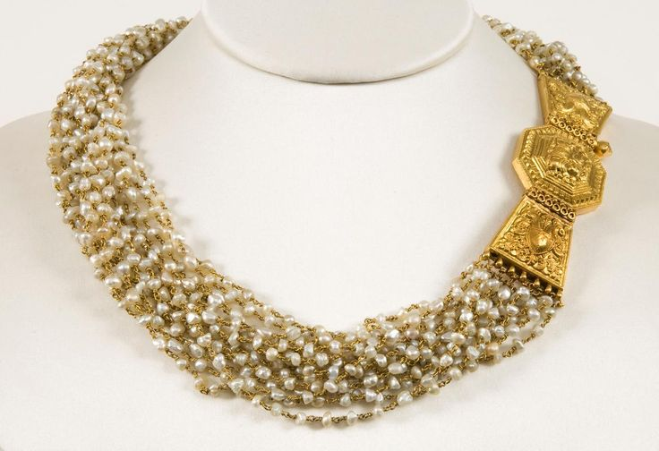 A necklace.  North India, first quarter 20th century.  Provenance: A necklace of several strings of Basra pearls and a gold clasp. The clasp is decorated with a Nandi and left and right a bird pattern.