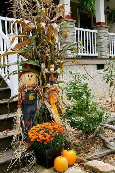 Cute autumn decor of a scarecrow, wheat, pumpkins, and mums in front of a porch