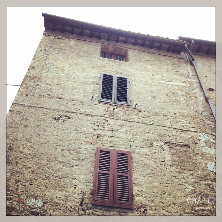 Stone building with red shutters Tuscany Italy by Grafthq.com