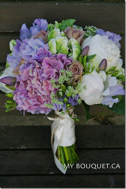 Pretty lavender, white, and green bridal bouquet featuring peonies, roses, hydrangea, queen anne's lace, freesia, and parrot tulips.