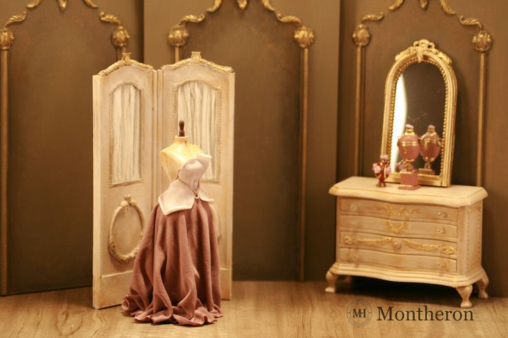 Miniature mannequin dressed in a cream and old pink evening gown.