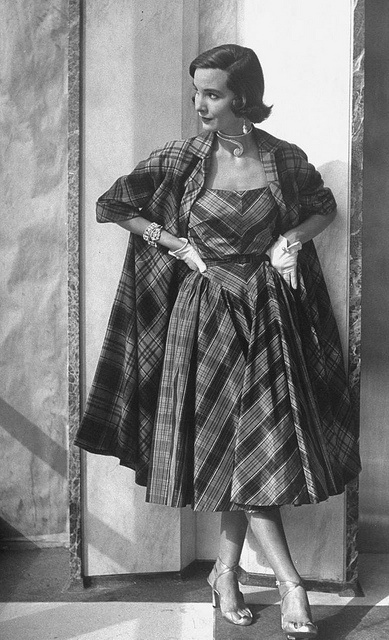 Using stripes to make a V in the elongated yoke, skirt gathered onto yoke sides, flaring from CF.    1950: Model wearing matching dress and coat.