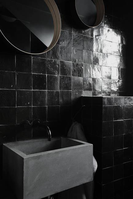 mirrored black tiles against a matte gray tub - dramatic bath space