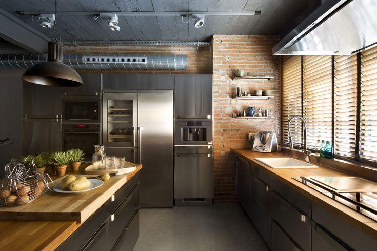 #reforma #cocina abierta en local rehabilitado con muebles y módulo de acero inoxidable, isla como separación, y suelo acabado microcemento.