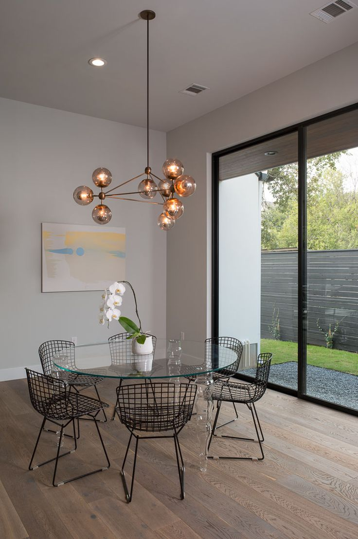 A Sculptural Glass Pendant Light Anchors The Round Glass Dining Table In  The Open Floor Plan