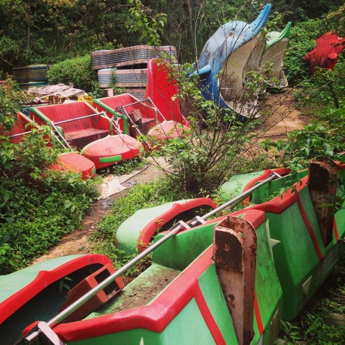 Shells of dolphin rides poke through vines, and a disused rollercoaster lays on its side at an abandoned amusement park in Nyarutarama, an area of Kigali, Rwanda