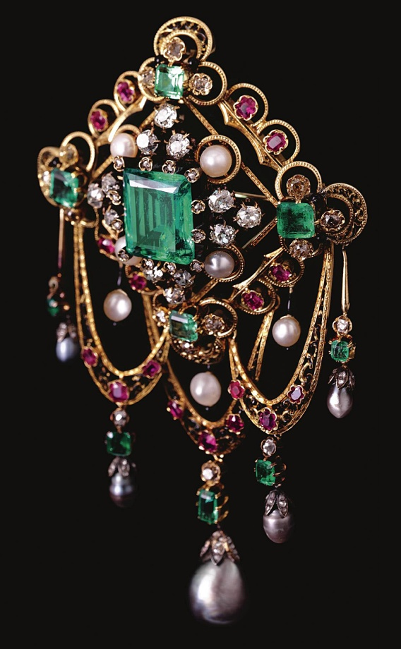 GEM-SET AND ENAMEL DEVANT DE CORSAGE , LAST QUARTER OF 19TH CENTURY Estimate: 30,000 - 50,000 CHF LOT SOLD. 49,000 CHF (Hammer Price with Buyer's Premium) Set with a step-cut emerald within pearls and circular-cut and cushion-shaped diamond clusters, further embellished by a black enamel frame, to the scrolling border of pink sapphire and circular-cut stones, suspending three articulated swags accented with pearls drops set en pampille
