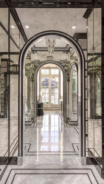 Glam Master Bathroom Features An Arched Doorway Framed By Antiqued Mirrored Walls Atop Gray Marble Floors