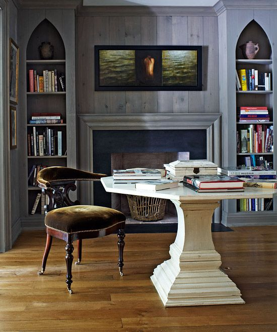 Rich hues create a mellow mood in this library. An elegant pedestal table multitasks as a desk or dining table - Traditional Home®  Photo: Virginia MacDonald