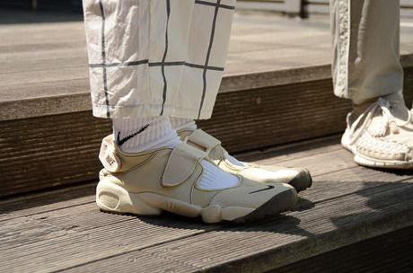 A tonally lovely combination of windowpane pants, beige Air Rifts, and white socks.