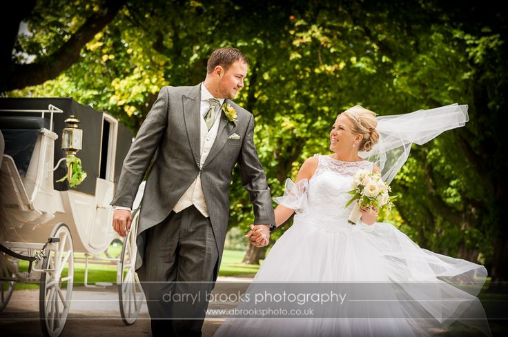 bride and groom walk  along a tree-lined path in East Park, Hull, with a horse-drawn carriage.