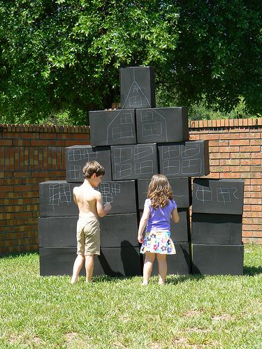 cardboard boxes, painted with chalk paint! Draw it, build it, knock it down, repeat! Allows for many levels of creative play.