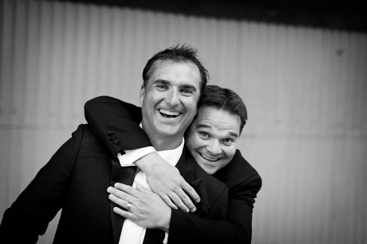 Groom and a groomsman have fun after a wedding at home at Milford beach, Auckland. Black and White.  beguiling fine art family photographs for the walls of the most discerning clients homes. We specialise in wedding and family portrait photography, and supply prints on the highest quality media, framed in beautiful conservation standard frames. We are a high end studio located in the beautiful city of Auckland, New Zealand.