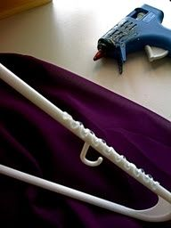 Use a hot glue gun to apply a zig zag pattern on plastic hangers to prevent  wide necked shirts from falling off