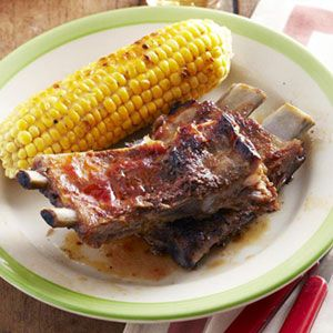 These ribs are coated in a spicy dry rub, then slathered with a tangy, vinegar-based sauce while cooking to add even more flavor. #MemorialDay #grilling