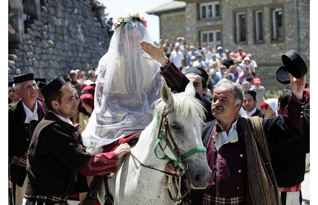"""Bride Danica Torteska is led on a horse to her husband by her father-in-law and the marriage witnesses, during a wedding ceremony in the village of Galicnik, some 150 km (93 miles) west of Macedonia's capital Skopje July 15, 2012. The Galicnik Wedding, a three-day traditional Macedonian wedding celebration held each """"Petrovden"""" or St. Peter's Day for a selected couple, involves traditional customs, costumes, and rituals and dances that have been passed down over the centuries."""