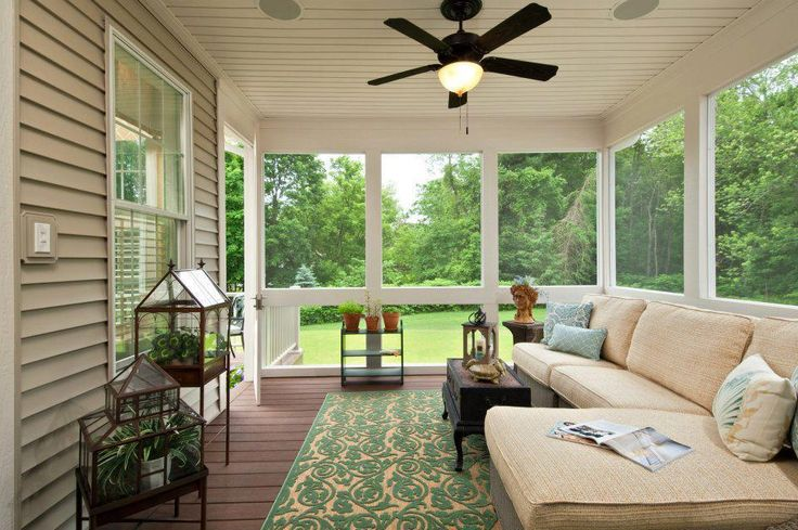 Screened in porch off the living room of the house used for outdoor entertaining.  A sectional, outdoor rug and transitional coffee table make the space inviting and comfortable for guests.