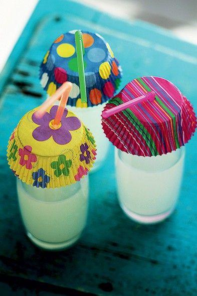 Para animar e colorir uma festa ao ar livre, uma boa dica é cobrir as bebidas com formas de cupcake deixando um buraquinho para o canudo. Além de dar charme ao ambiente, evitam que bichinhos entrem nas bebidas