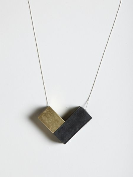faux/real: one + one necklace (brass + black rubber) Interesting combination of materials and positioning V necklace