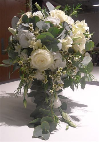 Traditional Teardrop Bridal Bouquet : Wedding bouquet flowers consist of cream roses, white lisianthus, wax flower and eucalyptus.