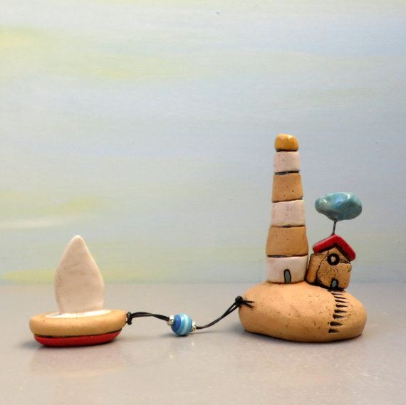 Dit is een een van een soort kleine gele en witte miniatuur vuurtoren met een miniatuur-boot, een kleine klei huis met een kleine wolk opknoping boven. Beide staan op een heuvel van gele klei. Er is een keramische bootje eraan verbonden zijn met een zwarte string, kleine decoratieve kralen compleet het landschap. Deze keramische vuurtoren en andere onderdelen zijn gemaakt van gele klei. Dit is een een van een soort handgemaakte home decor.  Ik schilderde deze miniaturen met zwart…