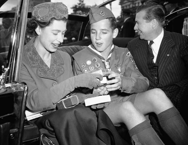 Eagle Scout John Rowsey of Arlington, Va., sits beside Queen Elizabeth II in an automobile at the White House in Washington D.C.  on Oct. 19, 1957, as he explains some gifts he is presenting on behalf of the National Capitol Council of Boy Scouts of America.