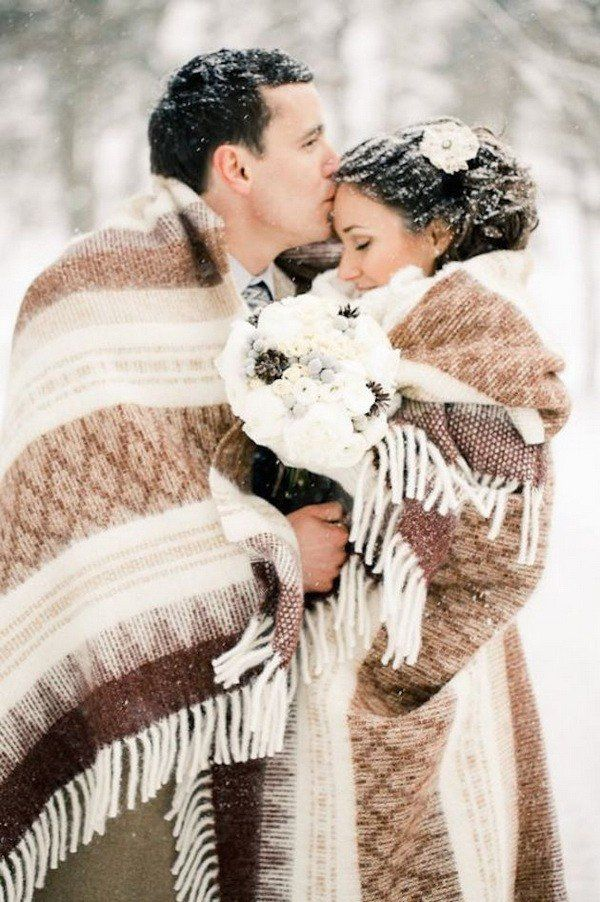 Cute couple hugging under blanket for winter wedding @myweddingdotcom