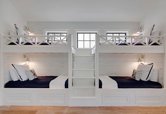 Bunk Room. White Bunk beds. White bunk bed with navy bedding. bunk room features two sets of white built-in bunk beds dressed in navy bedding lined with distressed shiplap flanked by a built-in staircase. #White #BunkRoom #Bunkbeds Old Seagrove Homes. #bunkerplans