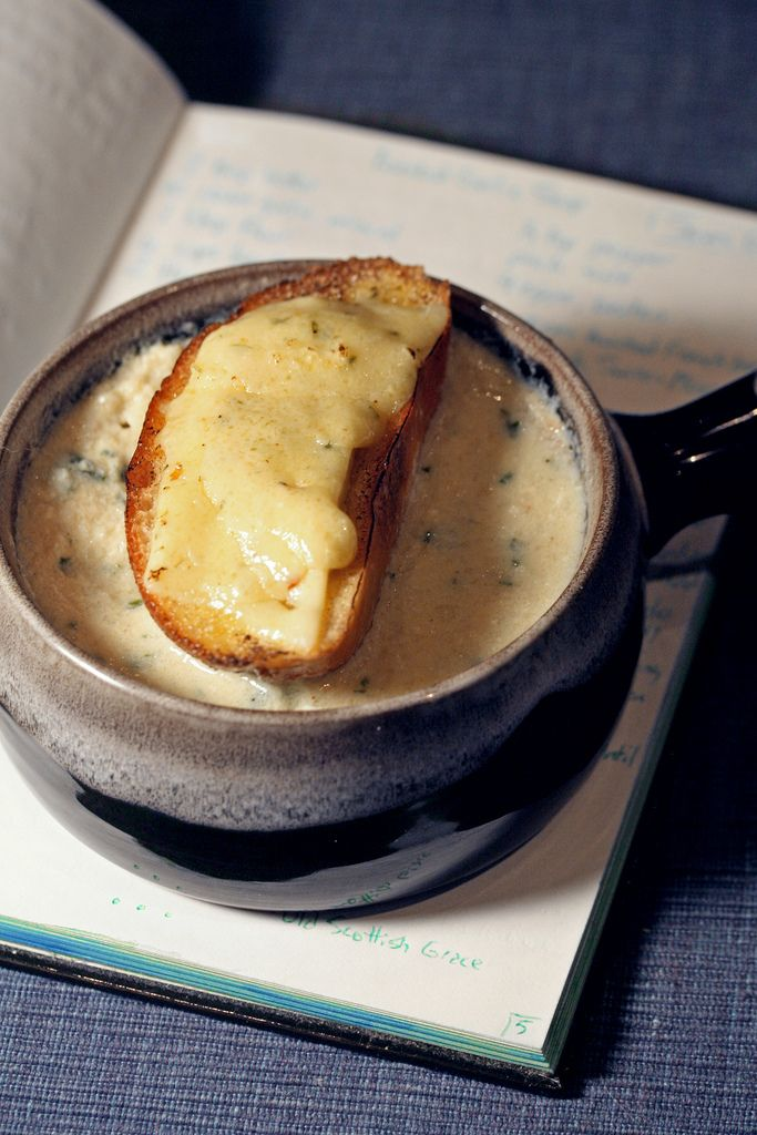 Toasted Garlic soup =   +2 tbsp butter  +10 cloves garlic, finely minced  +1 tbsp flour  +6 cups chicken or vegetable stock  +1/2 cup dry white wine  +4 eggs, beaten  +2 tbsp finely minced parsley  +Salt & pepper to taste  +6 slices slightly stale crusty bread  +1 cup crumbled chive-and-onion +Gloucester cheese