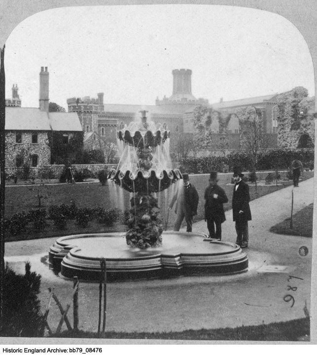 BB79/08476 A view showing three gentleman in top hats beside a fountain in Forbury Gardens, Reading, with Reading Gaol in the background.    Date1855 - 1860