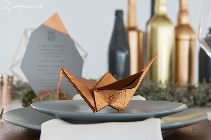 Copper origami crane used as wedding table stationery.