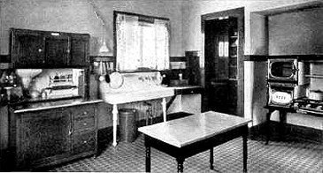 This kitchen has a separate cupboard, sink and cookstove. The Hoosier Cupboard on the left has a work surface and built-in flour sifter. The floor is linoleum. While the appliances are traditional, the triangle floor plan is strictly modern. 1915