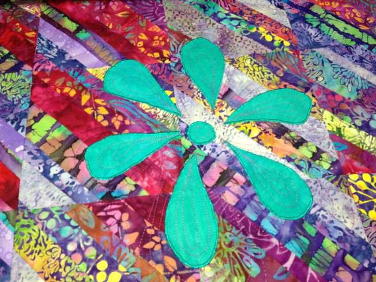 This is my first strata quilt.  I used batik and machine appliquéd flowers onto it using Ricky Tims hand dyed fabrics, very bright and I love it.