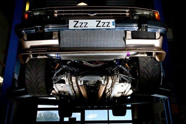 """Aliás, o interior todo foi modificado para ficar com uma aparência meio """"fora-da-lei"""", com alguns componentes originais — como a capa do painel — complementados por peças aftermarket, como o painel digital e os detalhes em fibra de carbono no revestimento das portas e um iPad. A suspensão e os freios também receberam atenção: a suspensão veio de um Ford Mustang SVT Cobra 2004 — eixo rígido com amortecedores pushrod na traseira, McPherson na dianteira — e os freios são da Porsche. Este cara…"""