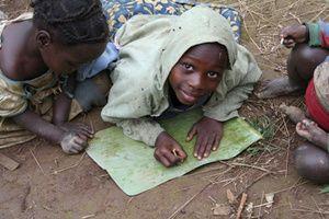 Denne dreng ser nåske glad ud - Men han er så fattig at hans familie ikke har råd til skoleredskaber og han må bruge et fiskeben og et bananblad til at lære at skrive på.  Som volontør kan du være med til at hjælpe børn som denne dreng