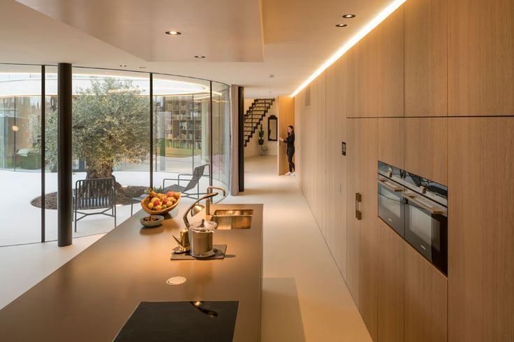 In this modern house, a wall of wood cabinets turns into the kitchen, with a large island. Hidden lighting at the top of the cabinets provides a soft glow to the space.