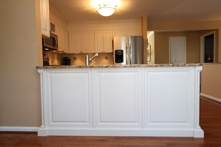 Transitional Style White Kitchen with Granite Countertops in Ellicott City, Maryland.  The decorative rope corner posts on the peninsula combine with the raised panel cabinets and crown molding to  bring a traditional influence to the otherwise clean and contemporary lines of this room.