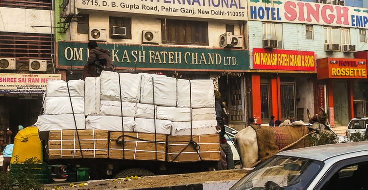 Cow pulling giant load of packages on a busy street in New Delhi.
